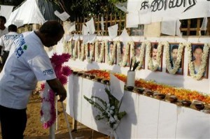 A member of the French aid group ACF places a wreath in front of the photographs of his slain colleagues at their memorial in Batticaloa