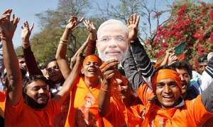 Narendra Modi mask held by supporters celebrating BJP victory in Gujarat elections in Ahmedabad